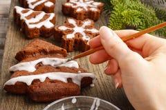 Adornamiento de las galletas del chocolate del pan de jengibre de la Navidad con el ic blanco Imagenes de archivo