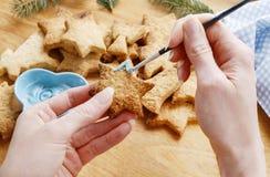 Adornamiento de las galletas del pan de jengibre con la formación de hielo azul y blanca Imágenes de archivo libres de regalías