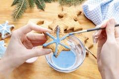Adornamiento de las galletas del pan de jengibre con la formación de hielo azul y blanca Fotografía de archivo libre de regalías