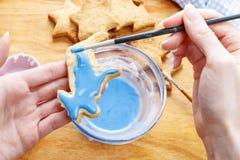 Adornamiento de las galletas del pan de jengibre con la formación de hielo azul y blanca Imagen de archivo libre de regalías