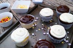 Adornamiento de las magdalenas del chocolate y de la vainilla Fotos de archivo libres de regalías