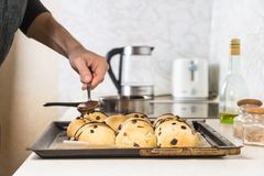 Adornamiento de los bollos cruzados calientes con el chocolate caliente Imagen de archivo libre de regalías
