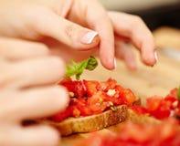 Adornamiento de los bruschettas del tomate con albahaca Imágenes de archivo libres de regalías
