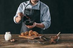 Adornamiento de los eclairs hechos en casa deliciosos con el chocolate y los cacahuetes Fotos de archivo