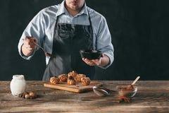 Adornamiento de los eclairs hechos en casa deliciosos con el chocolate y los cacahuetes Imagen de archivo libre de regalías