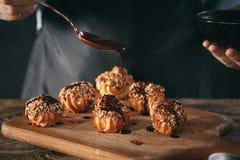 Adornamiento de los eclairs hechos en casa deliciosos con el chocolate y los cacahuetes Fotos de archivo libres de regalías