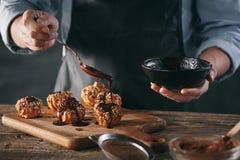 Adornamiento de los eclairs hechos en casa deliciosos con el chocolate y los cacahuetes Imagen de archivo