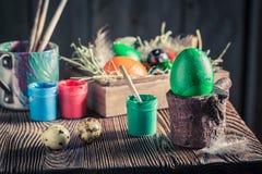 Adornamiento de los huevos de Pascua con el heno y las plumas Imagenes de archivo