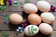 Adornamiento de los huevos de Pascua con las hojas Imagenes de archivo