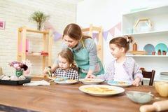 Adornamiento de los pasteles con las pequeñas hijas Foto de archivo libre de regalías
