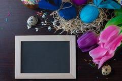 Adornamiento de Pascua Huevos de Pascua bajo la forma de conejo en la jerarquía con con la pizarra en un marco para escribir el t Imagen de archivo