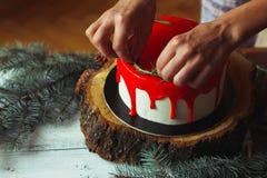 Adornamiento de proceso de la torta roja del ganache de la Navidad hecha en casa por las manos del ` s de la mujer con rozmarine  Imagen de archivo