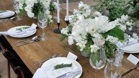 Adornamiento de tablas con los ramos de flores frescas con las velas y de decoración para una boda o de un partido para un banque metrajes