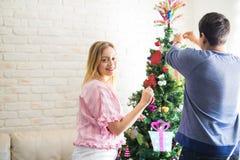 Adornamiento de un árbol de navidad con mi novio Foto de archivo