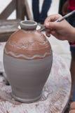 Adornamiento de un pote de arcilla mojado Imagen de archivo libre de regalías