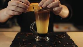 Adornamiento de una bebida del café helado con una rebanada anaranjada Un cierre para arriba almacen de metraje de vídeo