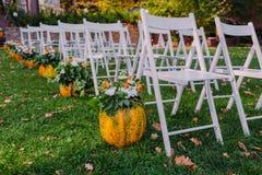 Adornamiento de una boda con la calabaza y las flores de otoño Ceremonia al aire libre en el parque Sillas blancas para las huésp Imagenes de archivo
