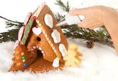 Adornamiento de una casa de pan de jengibre Imagen de archivo libre de regalías