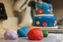 Adornamiento de una torta de cumpleaños con la pasta de azúcar coloreada Foto de archivo libre de regalías