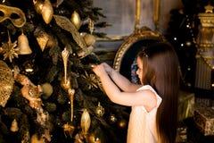 Adornamiento del árbol de navidad La muchacha viste para arriba el árbol de navidad Fotografía de archivo