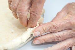 Adornamiento del borde de la pasta de Lorena de la quiche en el plato de la hornada Fotos de archivo libres de regalías