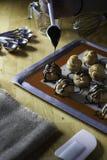 Adornamiento del ceam de los choux con la salsa de chocolate Fotografía de archivo