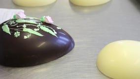 Adornamiento del chef de repostería de las manos de los huevos de chocolate de Pascua almacen de video