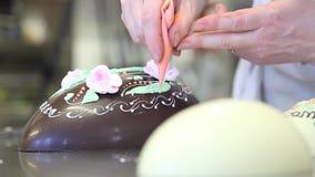 Adornamiento del chef de repostería de las manos de los huevos de chocolate de Pascua almacen de metraje de vídeo