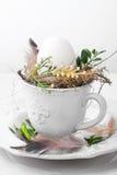 Adornamiento del huevo de Pascua en una taza Imágenes de archivo libres de regalías