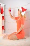 Adornan a la muchacha en el sombrero de santa con una chimenea Foto de archivo libre de regalías