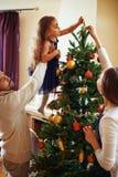 Adornando el árbol de Navidad junto Foto de archivo libre de regalías
