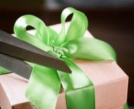 Adornando la caja de regalo con la cinta verde usando scissor Fotos de archivo
