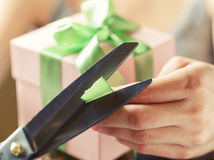 Adornando la caja de regalo con la cinta verde usando scissor Foto de archivo libre de regalías