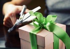 Adornando la caja de regalo con la cinta verde usando scissor Imagen de archivo libre de regalías