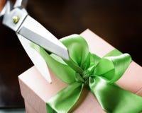 Adornando la caja de regalo con la cinta verde usando scissor Imágenes de archivo libres de regalías