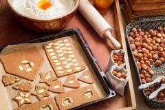 Adornando las galletas del pan de jengibre nuts momentos antes de la hornada Foto de archivo libre de regalías