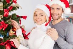 Adornando un árbol de navidad junto. Fotografía de archivo libre de regalías