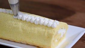 Adorne con la torta blanca poner crema del rollo dulce almacen de metraje de vídeo