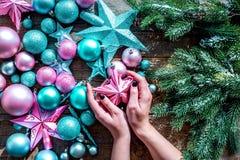 Adorne el árbol de navidad Juguetes de Navidad del control de las manos Las estrellas y las bolas cerca del pino ramifican en la  Fotos de archivo libres de regalías