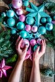 Adorne el árbol de navidad Juguetes de Navidad del control de las manos Las estrellas y las bolas cerca del pino ramifican en la  Foto de archivo libre de regalías