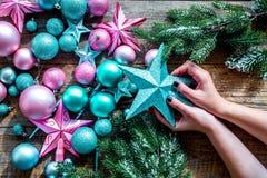 Adorne el árbol de navidad Juguetes de Navidad del control de las manos Las estrellas y las bolas cerca del pino ramifican en la  Fotos de archivo