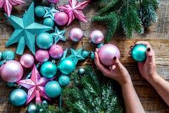 Adorne el árbol de navidad Juguetes de Navidad del control de las manos Las estrellas y las bolas cerca del pino ramifican en la  Imagenes de archivo