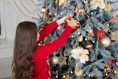 Adorne el árbol de navidad La muchacha del pequeño niño le gusta el presente de Navidad Navidad El niño disfruta del día de fiest imagen de archivo