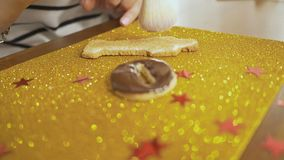 Adorne el pan de jengibre con el esmalte del chocolate usando un cepillo Una mano del ` s de la mujer hace una miga de la formaci almacen de metraje de vídeo