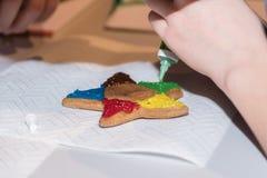 Adorne el pan de jengibre con la formación de hielo colorida Foto de archivo libre de regalías