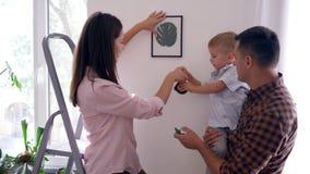Adorne interior, el niño agradable con los padres de medición de las ayudas de la ruleta repara en el apartamento y cuelga la ima almacen de video