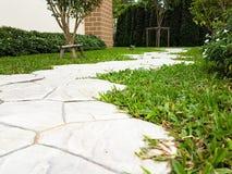 Adorne la calzada en el jardín con la hierba verde Foto de archivo