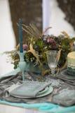 Adorne la placa y el vidrio de la boda con las flores y la nieve del invierno Fotografía de archivo libre de regalías