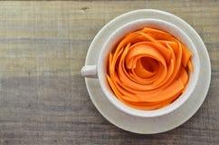 Adorne la taza con las zanahorias de las rebanadas en la tabla de madera Fotos de archivo libres de regalías