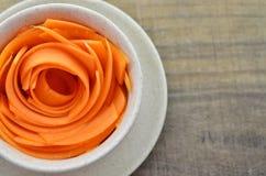 Adorne la taza con las zanahorias de las rebanadas en la tabla de madera Imagen de archivo libre de regalías
